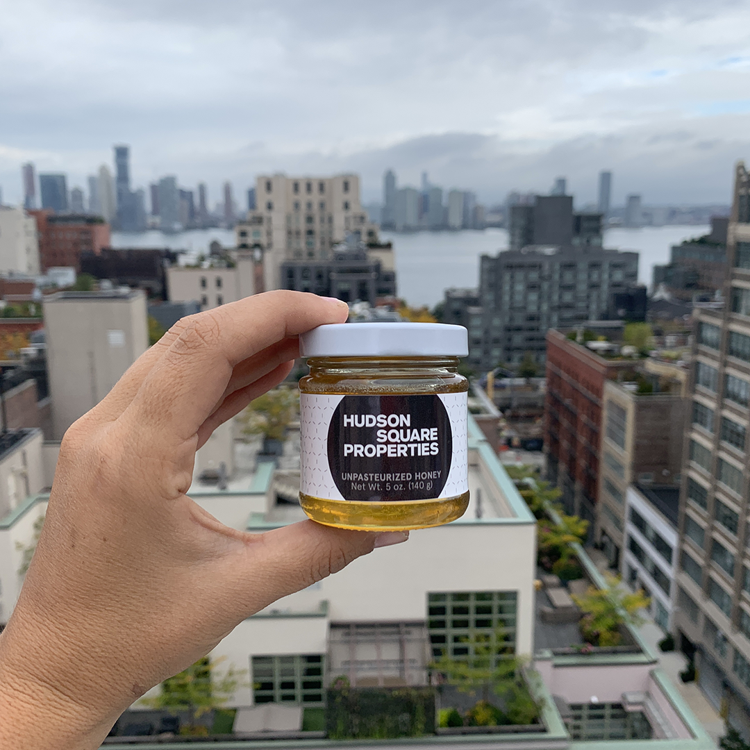 A man's hand holds a honey jar with Hudson Square Properties' company logo label on it against New York City's skyline in the background.